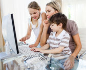 Attentive mother teaching her children how to use a computer — Stock Photo