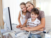 Caring mother and her children at a computer — Stock Photo