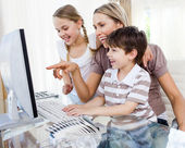 Children and their mother using a computer — Stock Photo