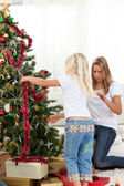 Blond little girl and her mother decorating Christmas tree — Stock Photo