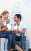 Couple eating while renovating their new house — Stock Photo
