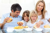 Joyful family eating hamburgers — Stock Photo