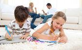 Koncentrerad syskon ritning liggande på golvet — Stockfoto