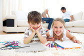 Smiling siblings drawing lying on the floor — Stock Photo