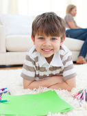 Portrait of little boy drawing lying on the floor — Stock Photo