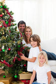 Happy family decorating a Christmas tree with baubles — Stok fotoğraf