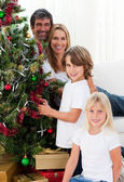 Portrait of a happy family decorating a Christmas tree — Stock Photo