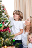 Mother and her children decorating a Christmas tree — Stock Photo