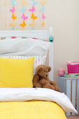 Child's bedroom with a teddy bear on the bed — Stock Photo