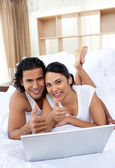 Couple with thumbs up using a laptop — Stock Photo