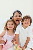 Pozorný matku a její děti si hrají s hračkami, kostky — Stock fotografie