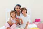 Attractive mother and her children playing with letters blocks — Stock Photo