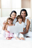 Young family using a laptop on the bed — Stock Photo