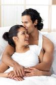 Giovane uomo baciare la sua ragazza sdraiata sul letto — Foto Stock