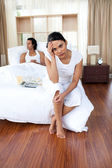Upset couple sitting on the bed separately — Stock Photo