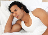 Angry man lying in the bed — Stock Photo