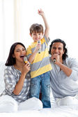 Lively young family singing with microphones — Stock Photo