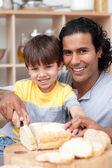 Padre sorridente aiutare suo figlio a tagliare il pane — Foto Stock