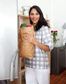Brunette woman unpacking grocery bag — Stock Photo