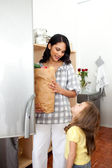 Cheerful little girl unpacking grocery bag with her mother — Stock Photo