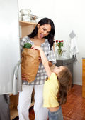 Blond little girl unpacking grocery bag with her mother — Stock Photo
