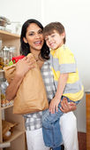 Adorable Little boy unpacking grocery bag with his mother — Stock Photo