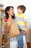 Cute Little boy unpacking grocery bag with his mother — Stock Photo