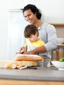 Charming father cutting bread with his son — Stock Photo
