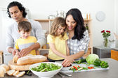 Positive family preparing lunch together — Stock Photo