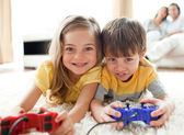 Adorable siblings playing video game — Stock Photo