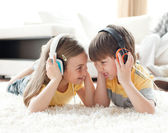 Siblings playing on the floor with headphones — Stock Photo