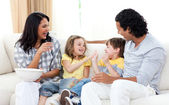 Loving family watching TV on sofa — Stock Photo