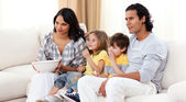 Smiling family watching TV on sofa — Stock Photo