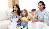 Cute siblings watching TV with their parents — Stock Photo