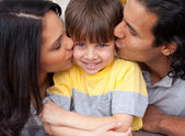 Close-up of parents kissing their son — Stock Photo