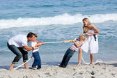 Cheerful family playing tug of war — Stock Photo