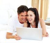 Affectionate couple using laptop — Stock Photo
