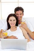 Smiling couple drinking orange juice — Stock Photo