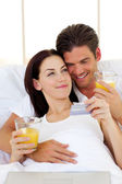 Intimate couple drinking orange juice — Stock Photo