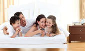Joyful family having fun in the bedroom — Stock Photo