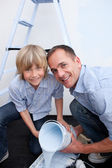 Portrait of smiling father and his son preparing paint — Стоковое фото