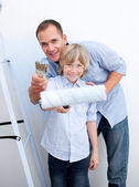 Smiling father and his son holding paintbrush — Stock Photo