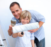 Close-up of a father and his son holding paintbrush — Stock Photo