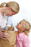 Smiling mother and her daughter unpacking grocery bag — Stock Photo