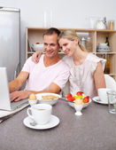 Enamored couple using a laptop while having breakfast — Stock Photo