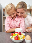 Adorable little girl eating fruit with her mother — Stock Photo