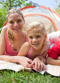 Carring mother and her little girl lying on the grass — Stock Photo