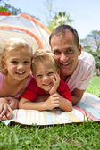 Happy father and his children lying on the grass — Stock Photo