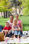 Smiling family having a picnic in a park — Stock Photo