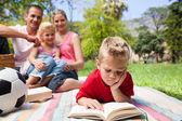 Koncentrat blond chłopiec czytanie podczas pikniku z jego fa — Zdjęcie stockowe
